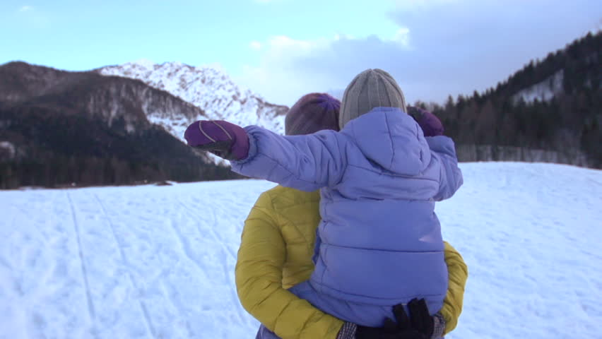 Slow Motion Rear View Of A Mother Carrying Her Little Son Piggyback While On The Walk Towards Snow Covered Mountains | Shutterstock HD Video #8195836
