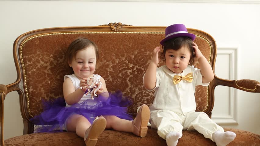 Baby boy and girl sit on couch with toy crown and hat | Shutterstock HD Video #8214067