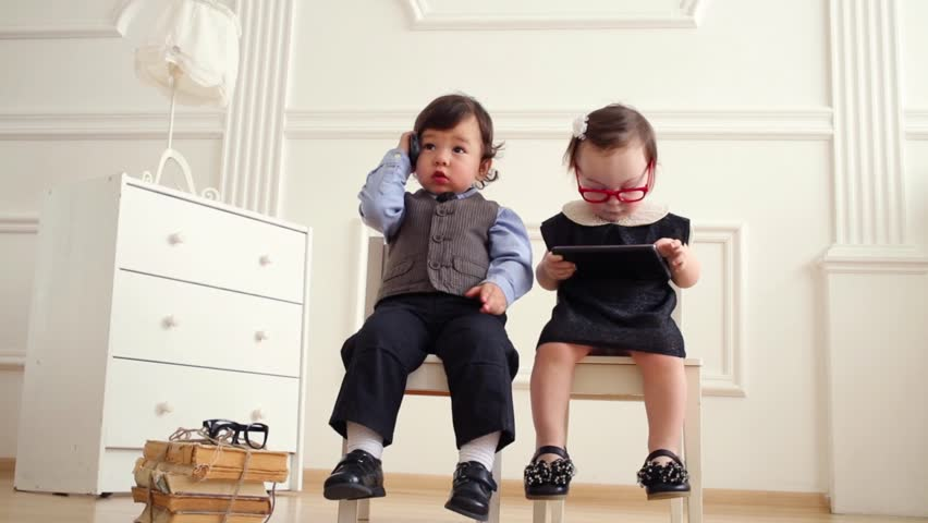 Baby boy with phone and baby girl in glasses with tablet PC sit on chairs
