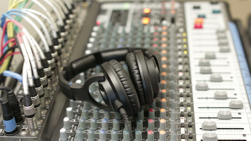 A mixing console with studio headphones is follow through focus from near to far side in this quick smooth shot. | Shutterstock HD Video #8220790