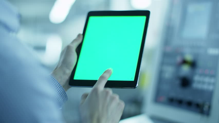Worker is Using Tablet PC with Green Screen in Portrait Mode in Factory. Great For Mock-Up Usage. Shot on RED Cinema Camera in 4K. ProRes codec - Great for editing, color correction and grading.