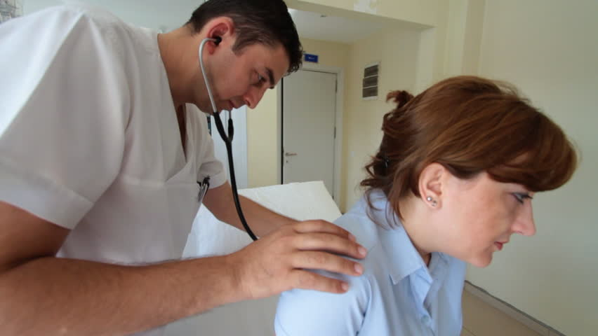 Male doctor checks patient's lungs using stethoscope
