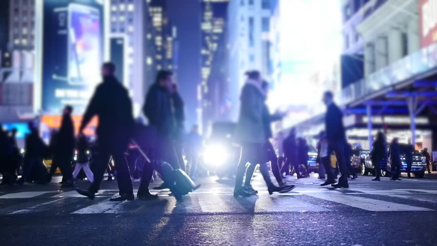 people crossing crosswalk in city. new york city night lights background