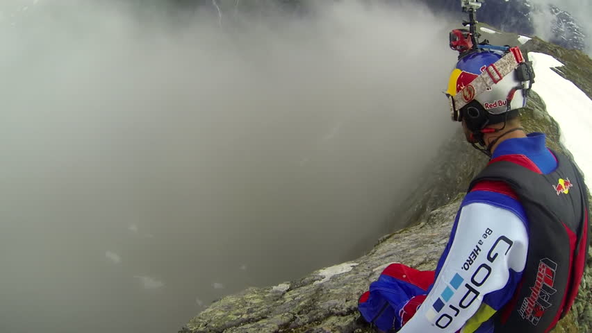 A base jumper in a wingsuit jumps down from a cliff, gliding down over a green mountain landscape, POV