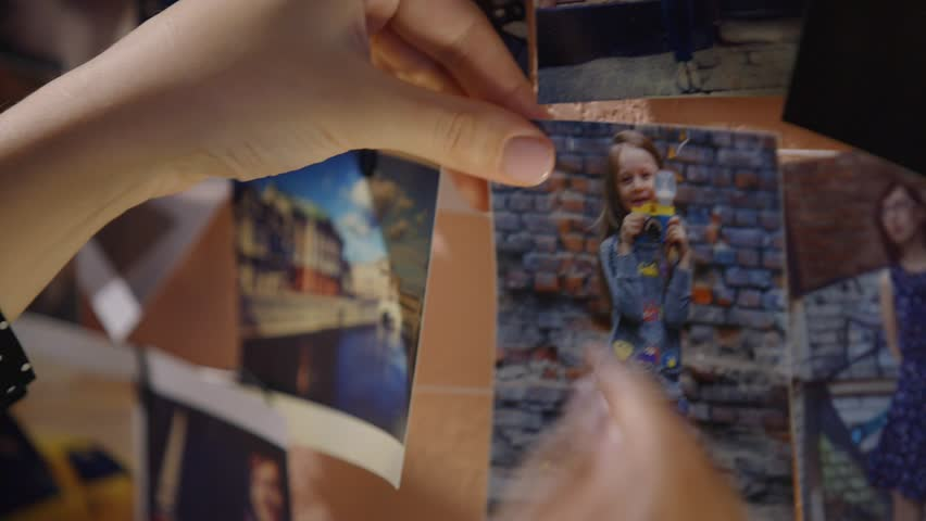 Woman hanging photo of her daughter on the wall, family photos
