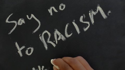 a person writing on a black cardboard slate with a chalk ' say no to racism, we are humans '