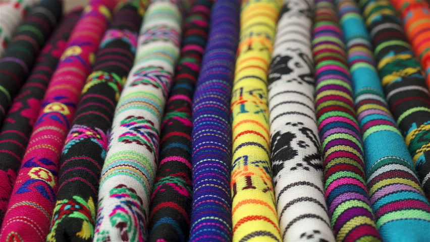 Close up shot of an anonymous woman rubbing her hand across traditional Mexican fabric with ethnic inspired designs and colors before making a purchase or decision about the piece that she wants.