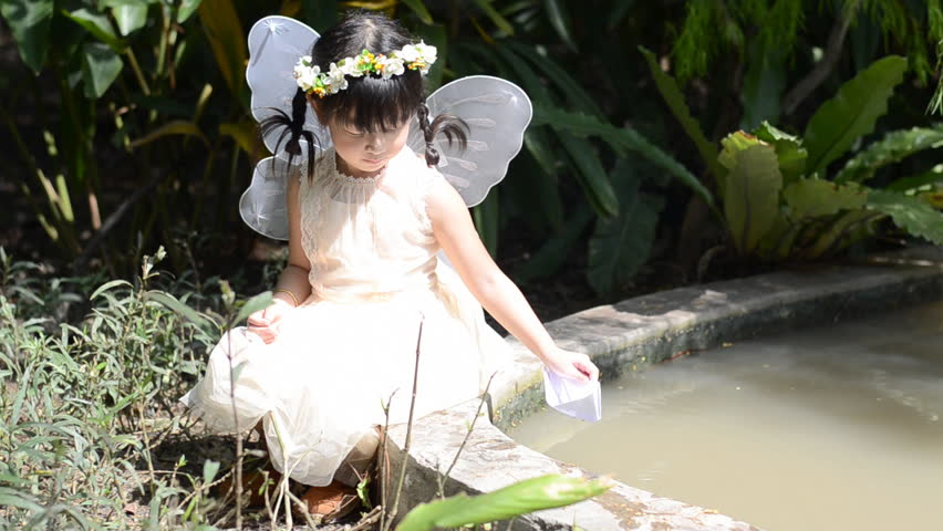 Little girl floating paper boat in the park | Shutterstock HD Video #8294572
