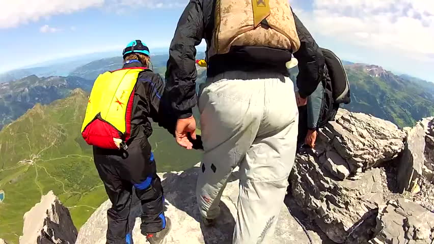 A group of base jumpers base jumping in a mountain landscape, jumps down from the edge of a cliff as one base jumper watches from above, POV