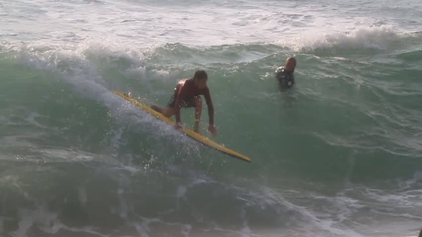 A surfer paddles the longboard, tries to ride the wave but loses and falls as the wave starts to rise   Shutterstock HD Video #8302987
