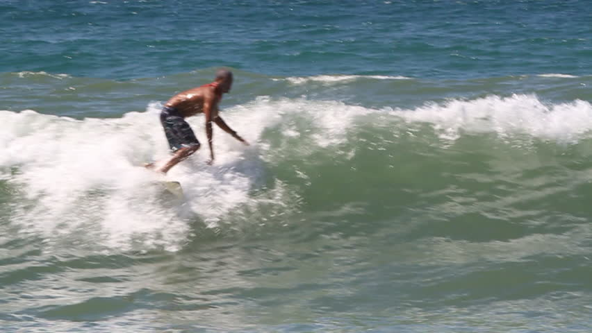 A surfer performs an aerial maneuver, tries to maintain balance but loses and falls into water   Shutterstock HD Video #8303338