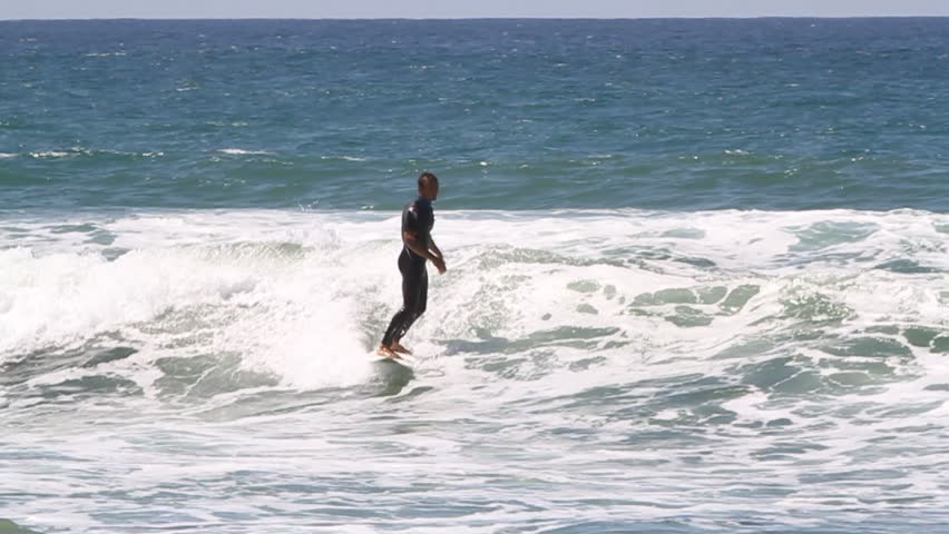 A surfer riding a small wave, tries to maintain balance but loses and falls into water   Shutterstock HD Video #8303449