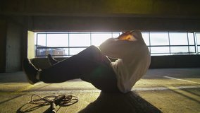 4K Slow motion clip of a hooded athlete finishing his workout with sit ups in a gritty urban environment, shot on RED EPIC