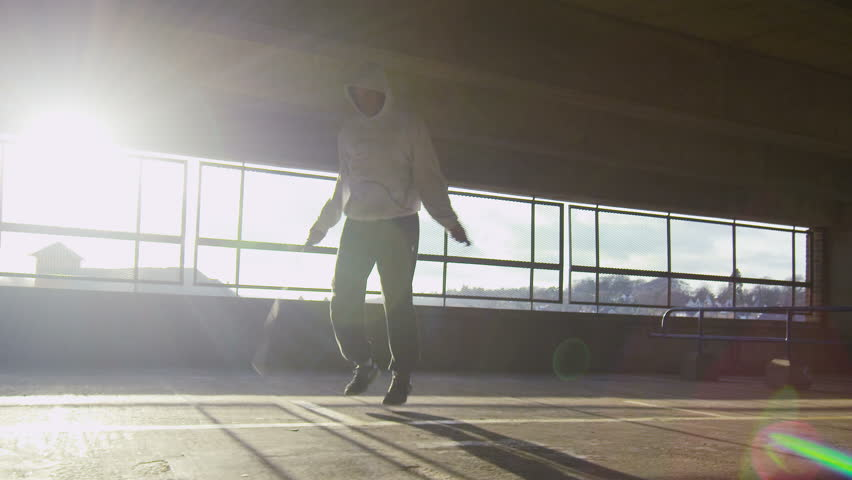 4K Slow motion tracking shot of a man jump roping in an urban environment during the day with sun flare, shot on RED EPIC