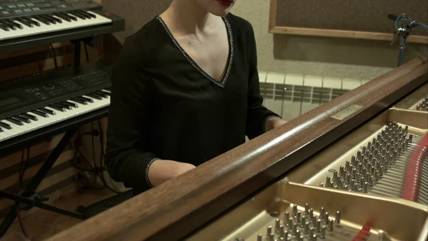 Beautiful girl playing the piano in a recording studio light slow motion   Shutterstock HD Video #8333515