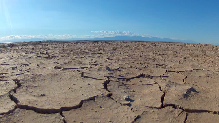 Close up zoom shot of cracks in the mud of a dried up lake bed. Drought conditions and lack of water and precipitation has led to many lakes drying up.   Shutterstock HD Video #8336233