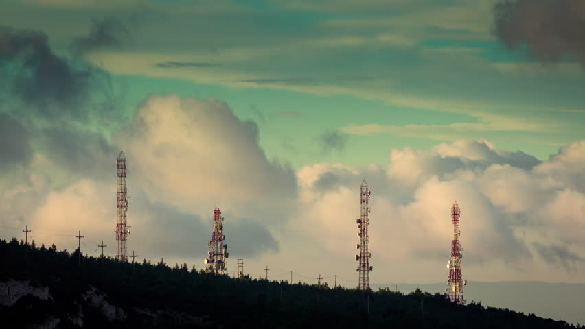 4K timelapse of communication and broadcast towers at the top of a mountain at sunrise with clouds passing low. Sequence has been de-flickered and all unwanted elements  have been digitally removed..