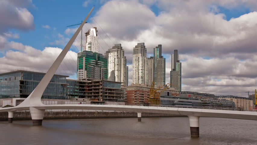 """Puente de la Mujer, a modern footbridge and landmark of Buenos Aires, Arg, in front of office buildings. Photo time-lapse with sunlight """"flashing"""" through dark clouds (C. 40D, DSLR).  