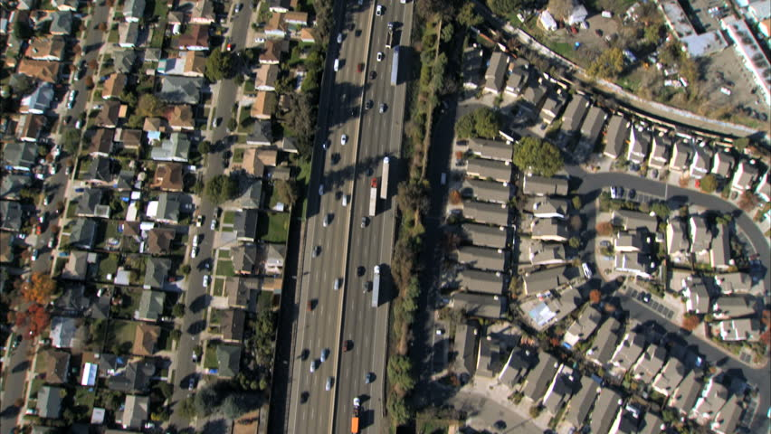 Aerial view of traffic on a freeway with suburban housing either side