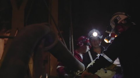 Miners and engineers checking map inside a mine