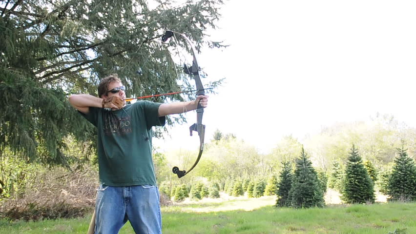 A bowman practices his archery skills outside by shooting his bow and arrow at a target.