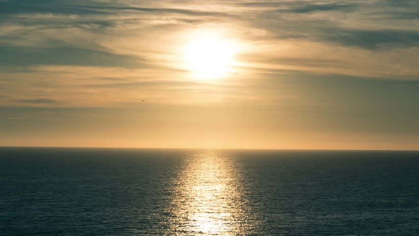 Sun Reflecting off Pretty Ocean Waves with Beautiful Clouds in Sky - Around Sunset - Sun Setting Soon over Horizon on Sea