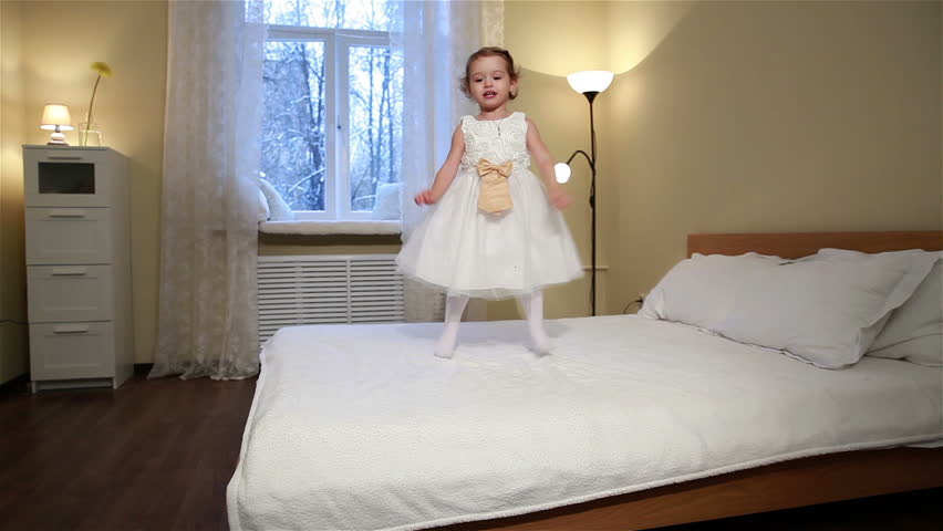Little fidget. Cute little girl in white dress jumping on the bed in the bedroom