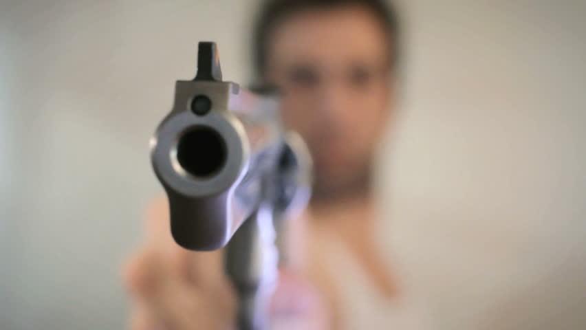 Man aims a gun at camera close up
