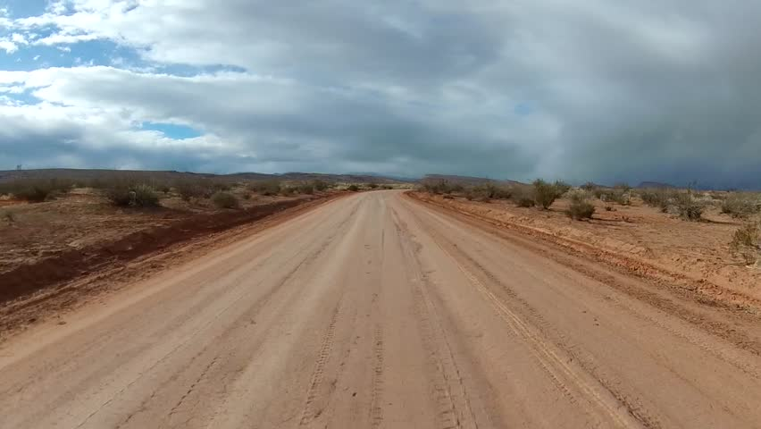 Off-road driving on high-desert road with winter storm in the distance. POV filmed in the desert southwest of St. George, UT along the Arizona border.