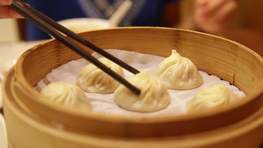 Xiao long bao / xiaolongbao soup dumplings. Woman eating Chinese Shanghainese steamed dumpling buns with chopsticks in restaurant in China. #8445019