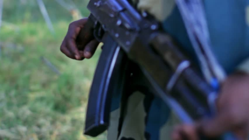 Ethiopian soldier holding AK 47 riffle aka Kalashnikov. Closeup with shallow deep of field shows riffle prepared to use.