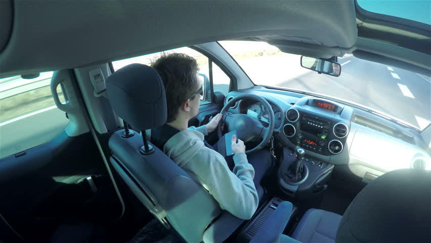 Man with glasses picks up the phone while driving car 4K. Driving car vehicle view from inside car below roof in the back, young attractive man steering wheel. Ultra-High definition video. | Shutterstock HD Video #8479447