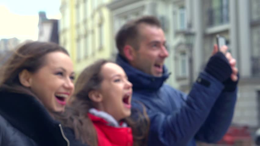 Young happy tourist family having tour walking in city. Amazed Girl showing landmarks. Enjoying sights of town. Man taking selfie photo outside. Tourism concept. Slowmotion 240 fps, 1080p | Shutterstock HD Video #8481496