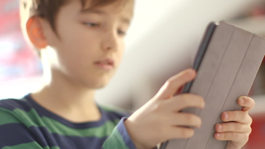 Young boy engrossed in playing games on a touchscreen tablet