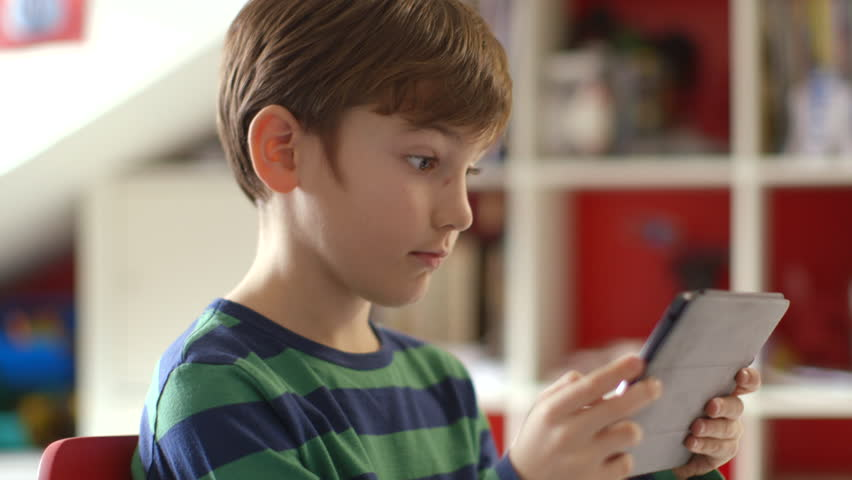 Young boy playing games on a touchscreen tablet