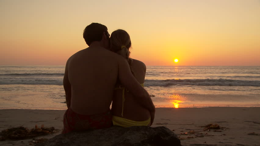 Back side of young couple kissing on beach at sunset | Shutterstock HD Video #854221