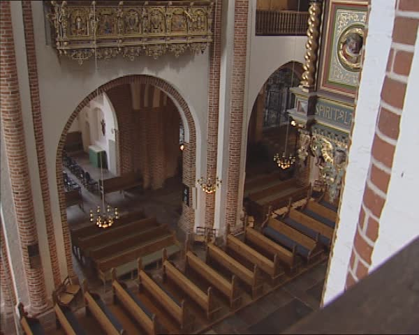 ROSKILDE CATHEDRAL, DENMARK - SEPT 2011: Looking down into the nave + tilt up Royal Gallery and the Renaissance Throne of Christian IV (royal pew) high up on the north wall opposite the organ. | Shutterstock HD Video #8550406