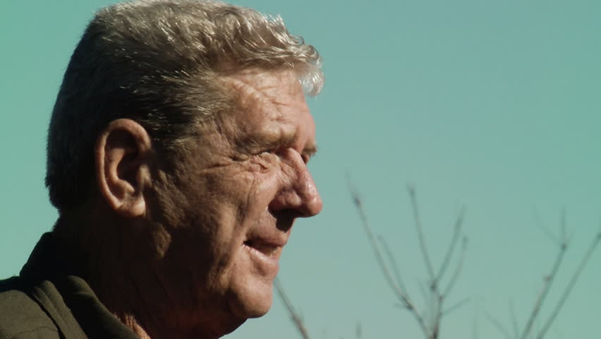 A pleasant elderly gentlemen smoking a cigarette outdoors with blue sky #8557093