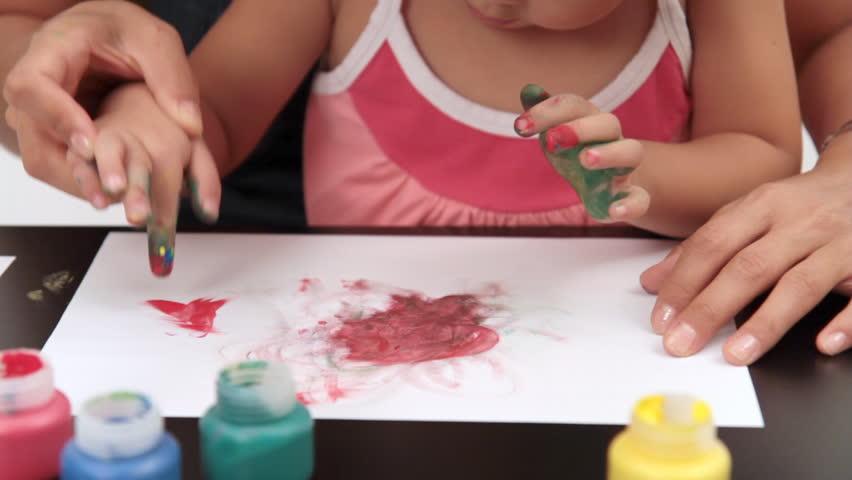 Mother helps her daughter fingerpaint