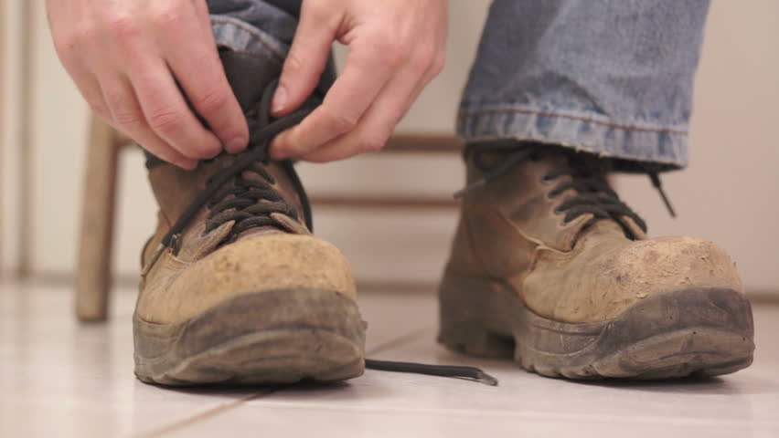 Low angle shot of an anonymous male sitting on a wooden chair and taking off his well worn, old, safety work-boot with steel toes.