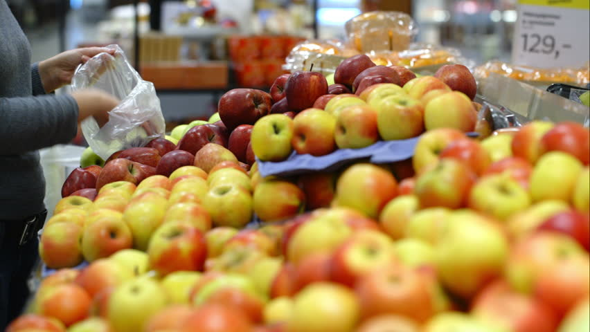 Woman in the supermarket coming up to the fruit counter. She choosing and putting apples in plastic bag   Shutterstock HD Video #8623381