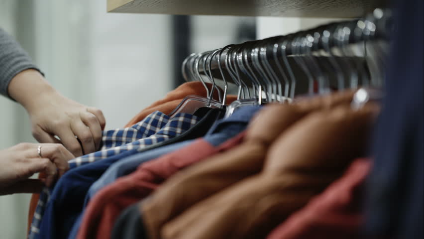 Woman in the shop looks through the male jackets and shirts, which are hanging on the racks | Shutterstock HD Video #8623483