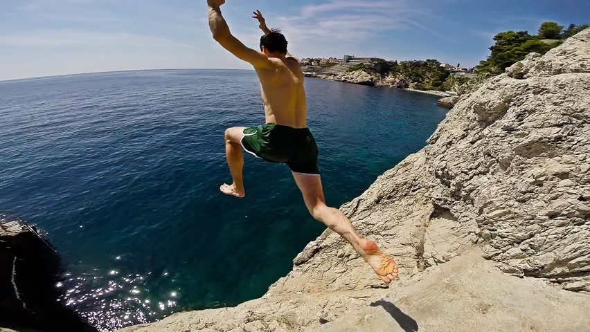 Athletic Young Man Jumping From Cliff Into Ocean Sea Water Muscular Adventure Extreme Sports Lifestyle Hobby Vacation Clear Beach Slow Motion Leisure Activity Gopro HD