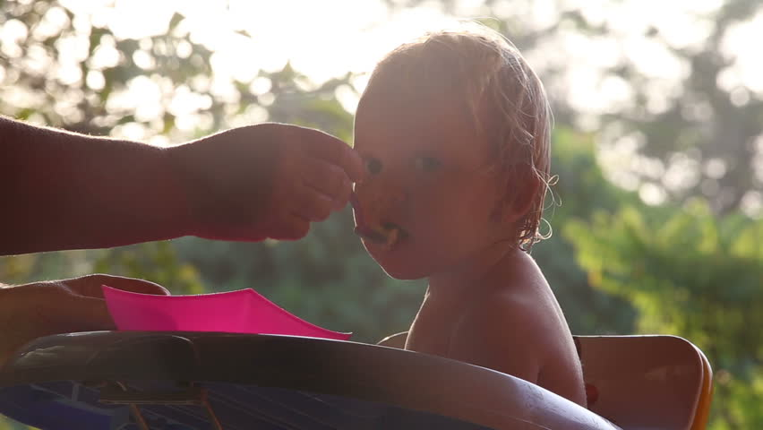 Small blonde baby girl feeding on the high chair at sunrise   Shutterstock HD Video #8631604