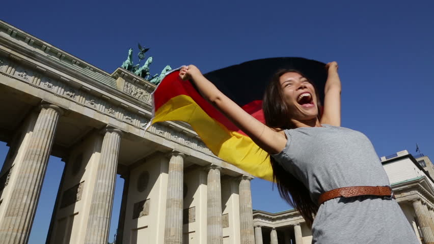 German flag - Woman happy at Berlin Brandenburger Tor cheering celebrating waving flag by Berlin Brandenburg Gate, Germany. Cheerful excited multiracial woman in Germany travel concept.