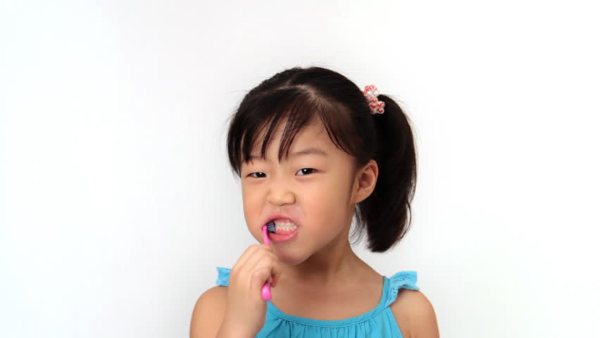 Little girl looks at camera and brushes her teeth