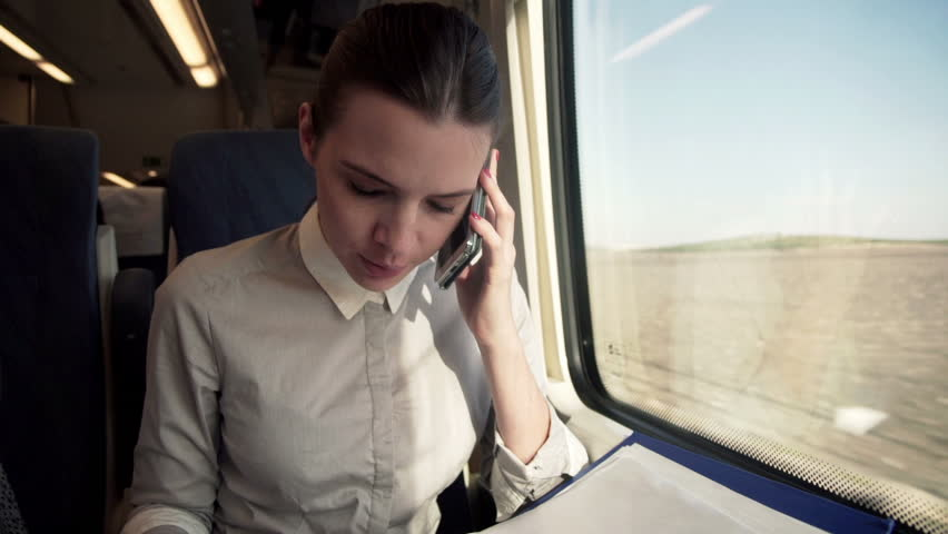 Businesswoman talking on cellphone and reading documents on a train
