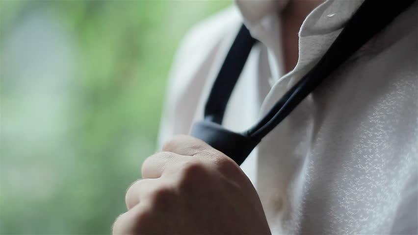 Man in white shirt tying a tie near the window. Close-up  | Shutterstock HD Video #8712253