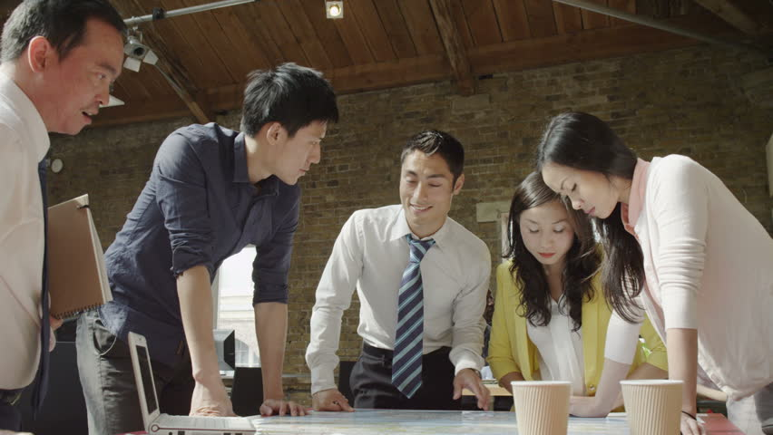 4K Asian business team in strategy meeting, looking at a map of the world | Shutterstock HD Video #8739388