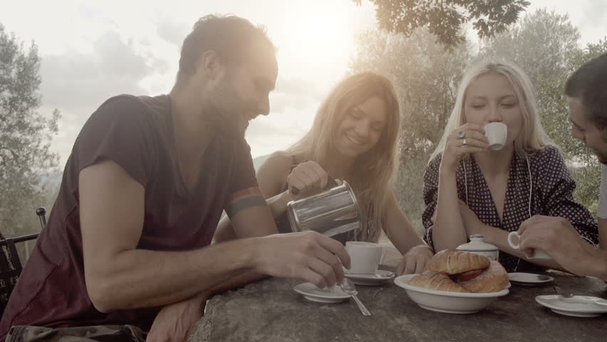 Group of four happy men and women friends smile, laugh and drink coffee during italian breakfast on a summer sunny day morning in tuscany, italy with visible sun - slow-motion dolly HD video footage | Shutterstock HD Video #8742301